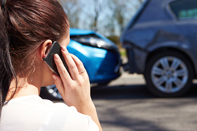 Woman on phone in front of car accident